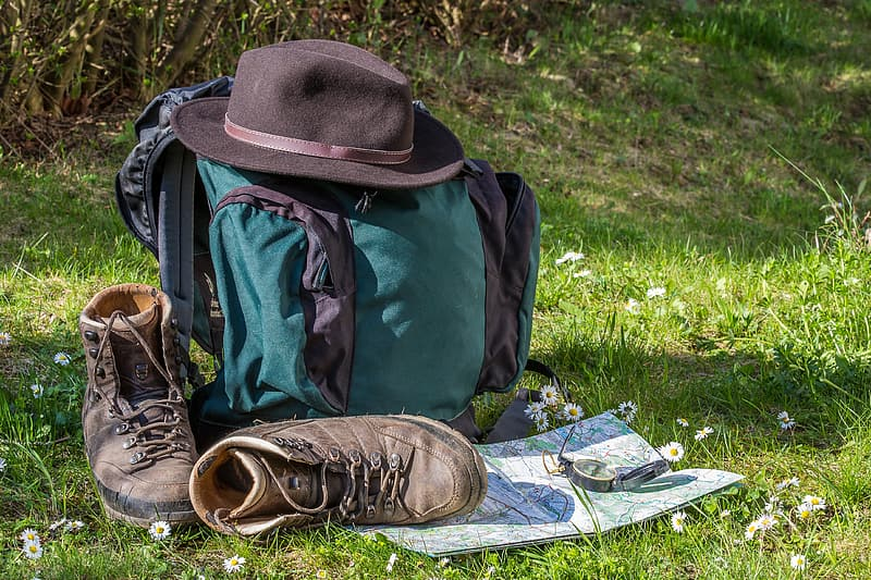 Black and green backpack and Fedora hat on green grassland