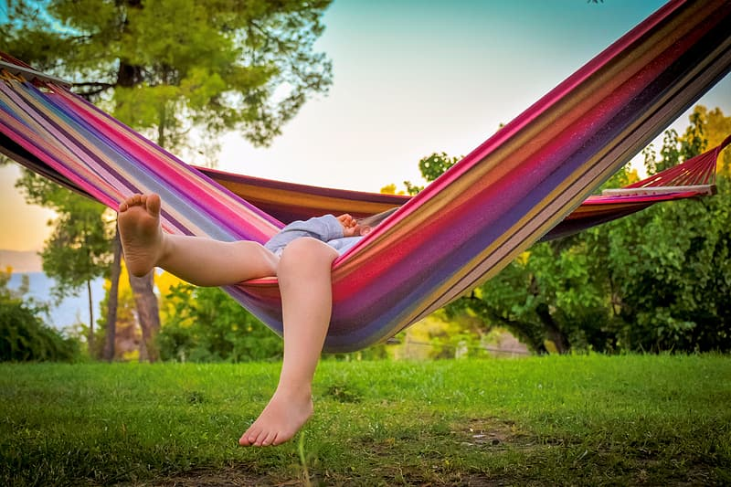 Person lying down on multicolored striped hammock