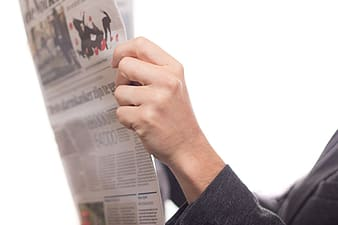 Person holding white newspaper