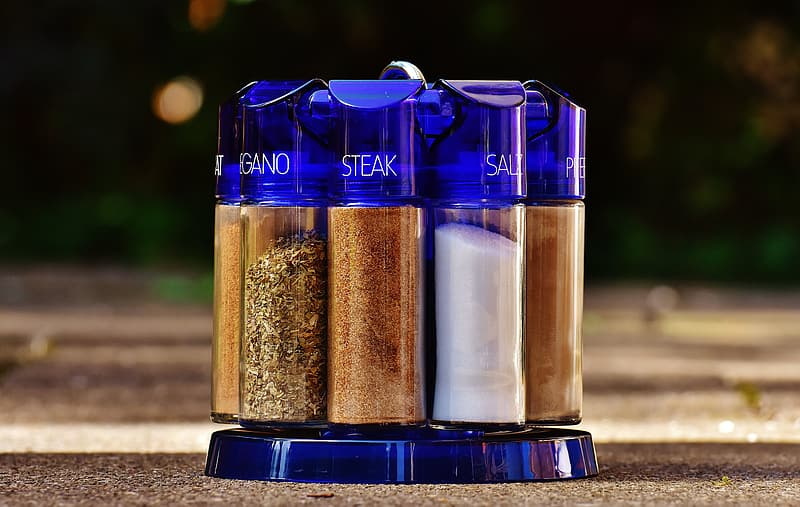 Purple glass spice rack with condiments on brown surface