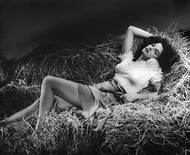 Woman lying down on haystack holding revolver