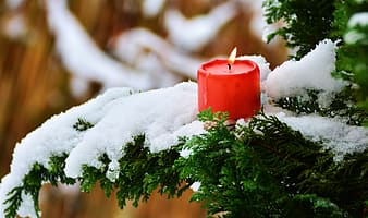 Red pillar candle on white snow