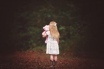 Girl in pink dress standing on dried leaves during daytime