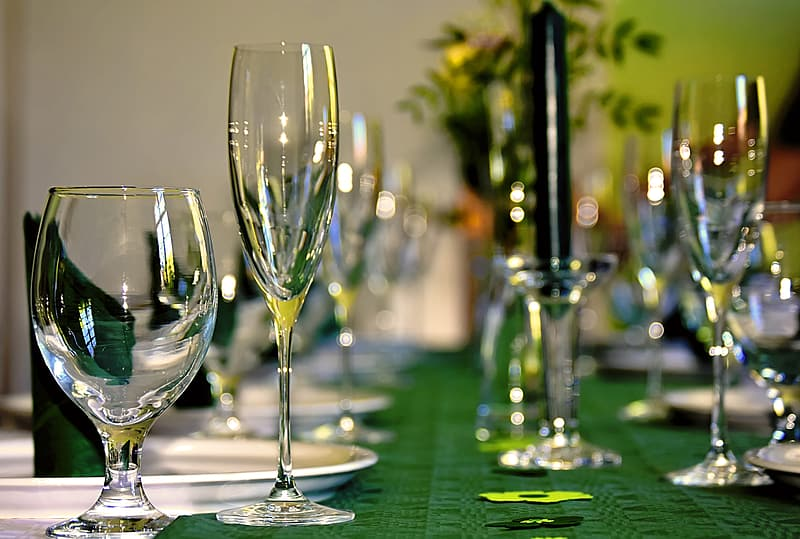 Clear wine glasses on green table cloth