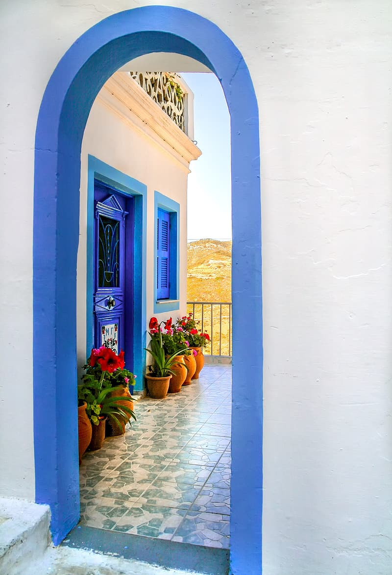 Blue painted closed door with flower arrangement outside