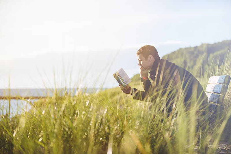 Man wearing blue jacket sitting on bench reading books facing body of water