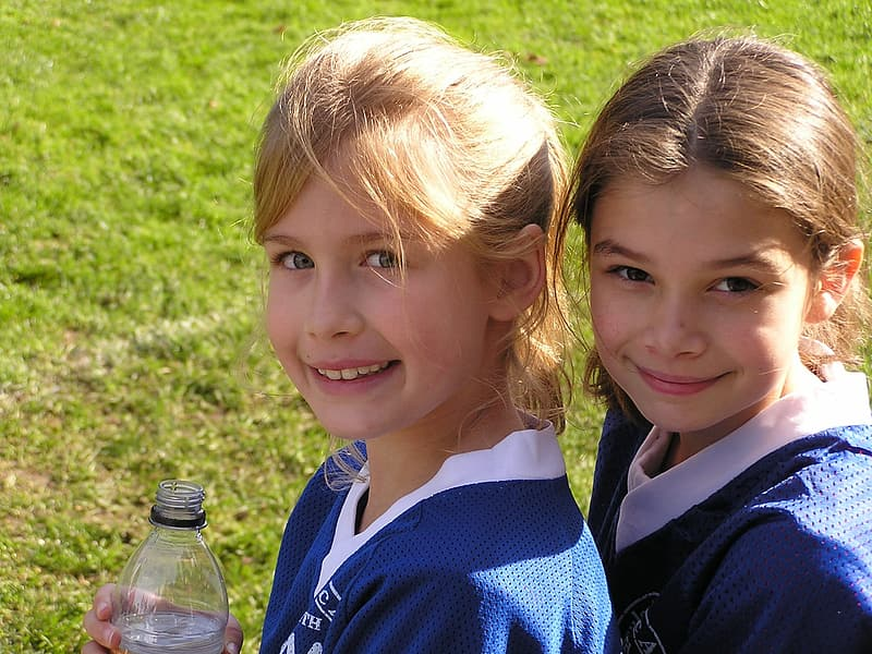 Two girl wearing white and blue v-neck shirts standing on green grass fields