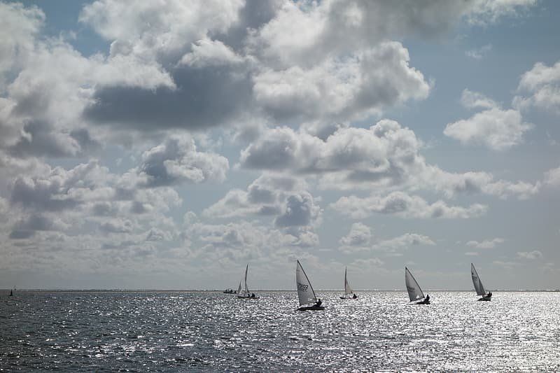 Sail boat on sea under cloudy sky during daytime