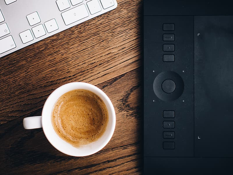 Flat lay photography of white ceramic mug filled with coffee beside black graphics tablet