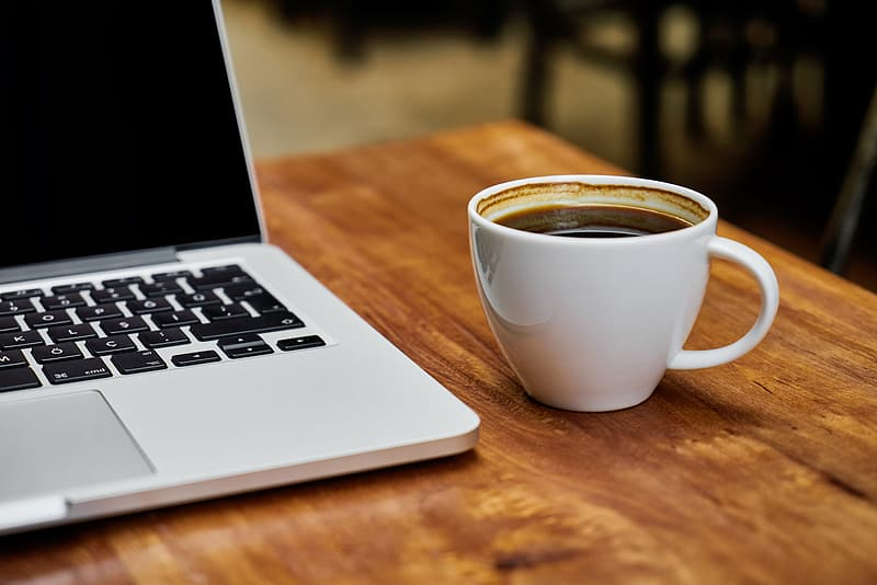 Coffee filled white ceramic mug beside MacBook Pro on top of brown wooden table
