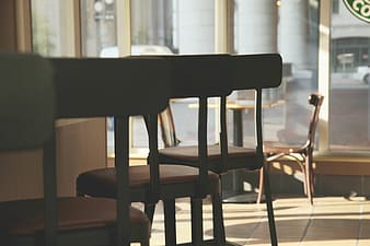 Low angle photography of three black-and-red leather-padded wood-framed bar stools