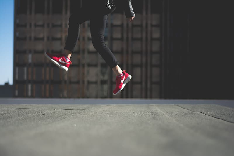 Person in black pants and red nike sneakers jumping on black asphalt road