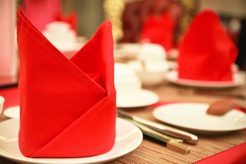 Selective focus photography of red table cloth on white ceramic plate