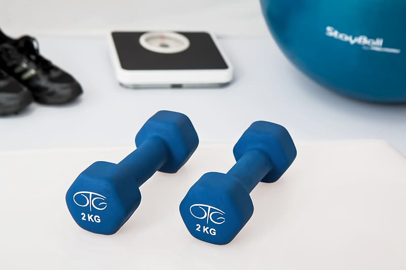 Two 2 kg. vinyl dumbbells on white surface
