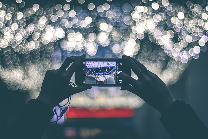 Person holding black smartphone taking photo of white lights
