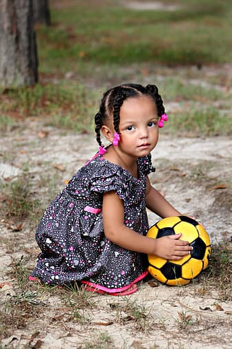 Girl wearing gray floral dress holding yellow soccer ball