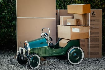 Classic green car loaded with brown cardboard boxes