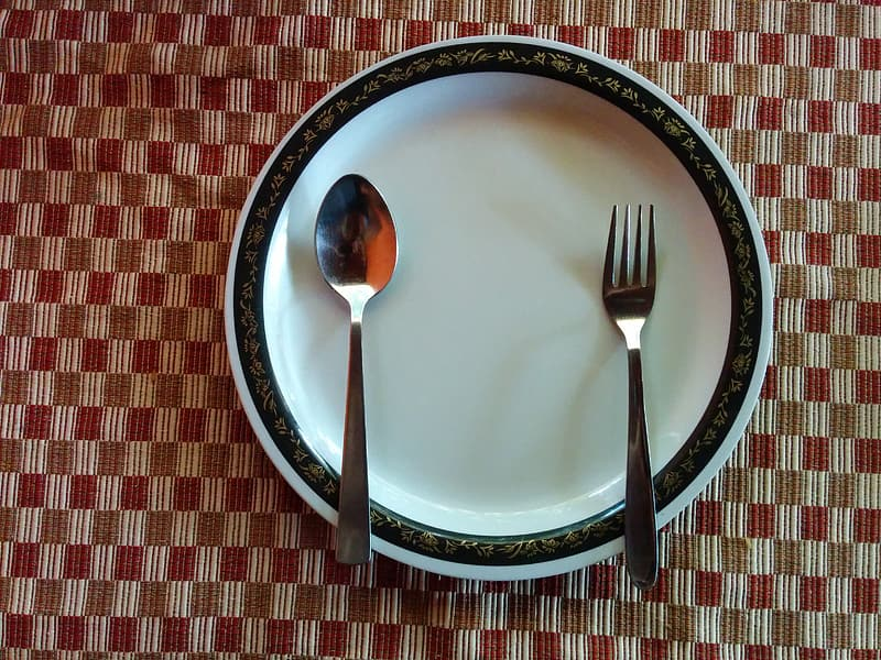 Silver fork and spoon on white ceramic plate