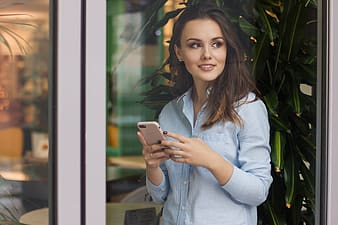 Woman in white dress shirt holding white smartphone