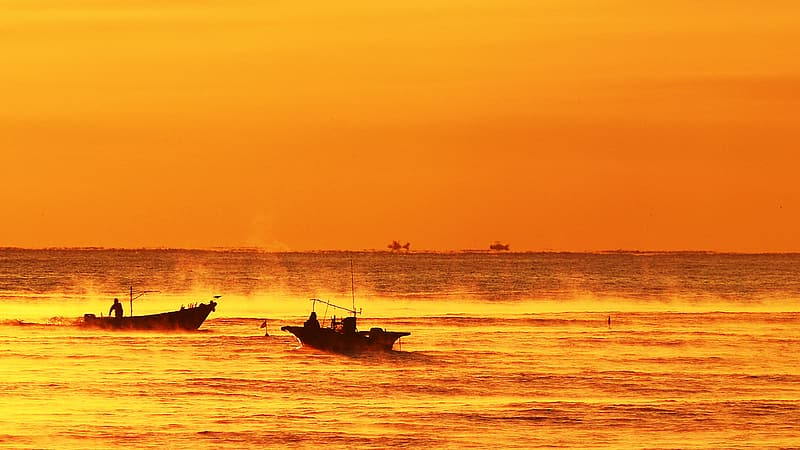 Silhouette of 2 people riding boat on sea during sunset