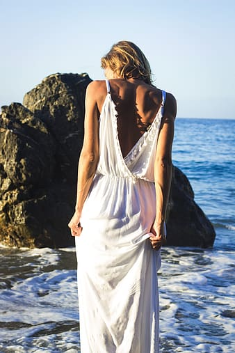 Woman wearing white dress facing the sea with rock formation