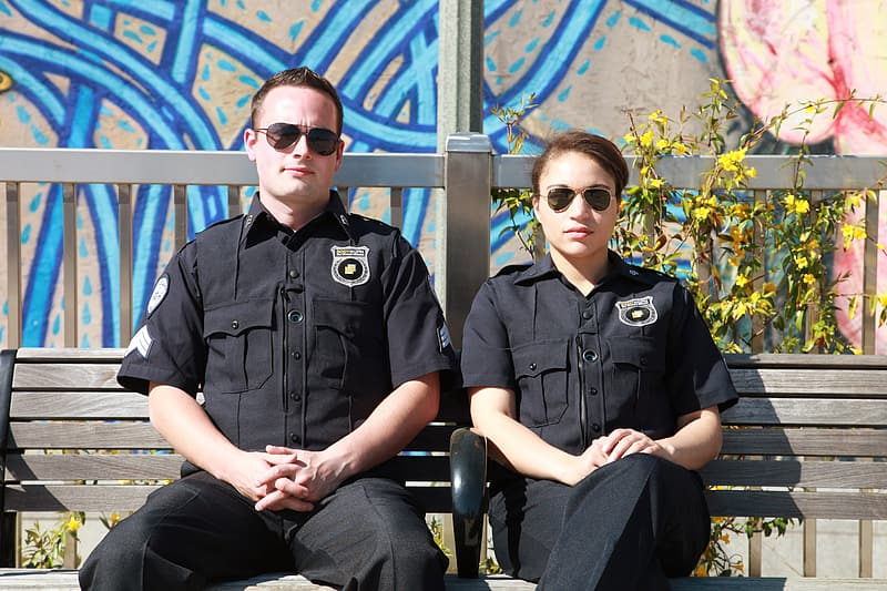 Two male and female police sitting on bench