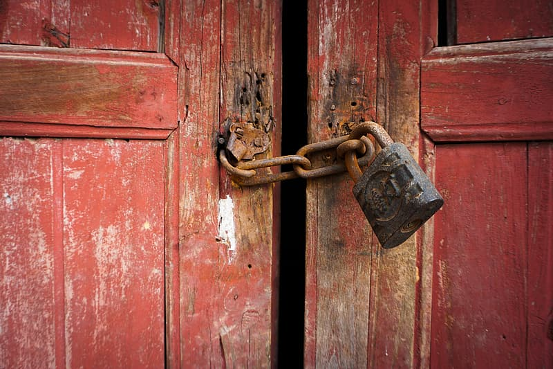 Closeup photo of rusted black and brown padlock with rusted brown keychain locked on brown wooden door panel