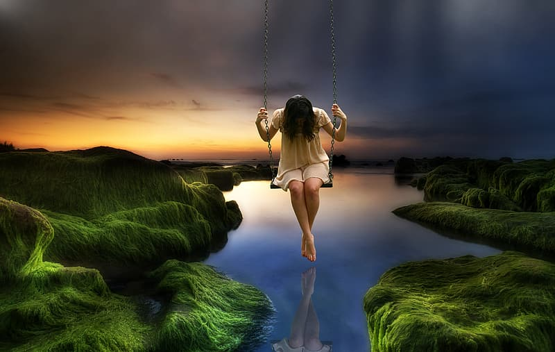 Woman on swing with lake on the background