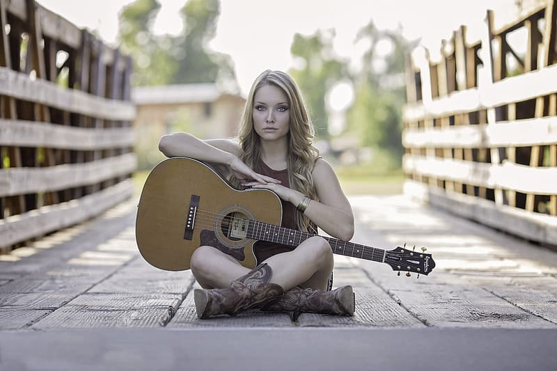 Selective focus photography of woman wearing sleeveless top holding cutaway acoustic guitar sitting on bridge