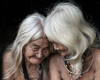 Two women wearing necklaces