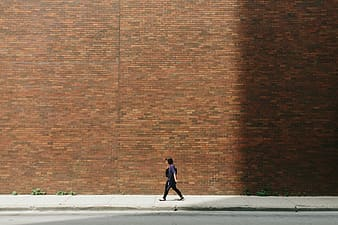 Woman walking down the street along red brick wall