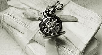 Grayscale photography of pocket watch on books