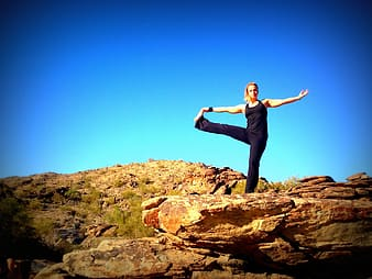 Woman wearing black tank top and pants standing on rock formation under clear blue sky