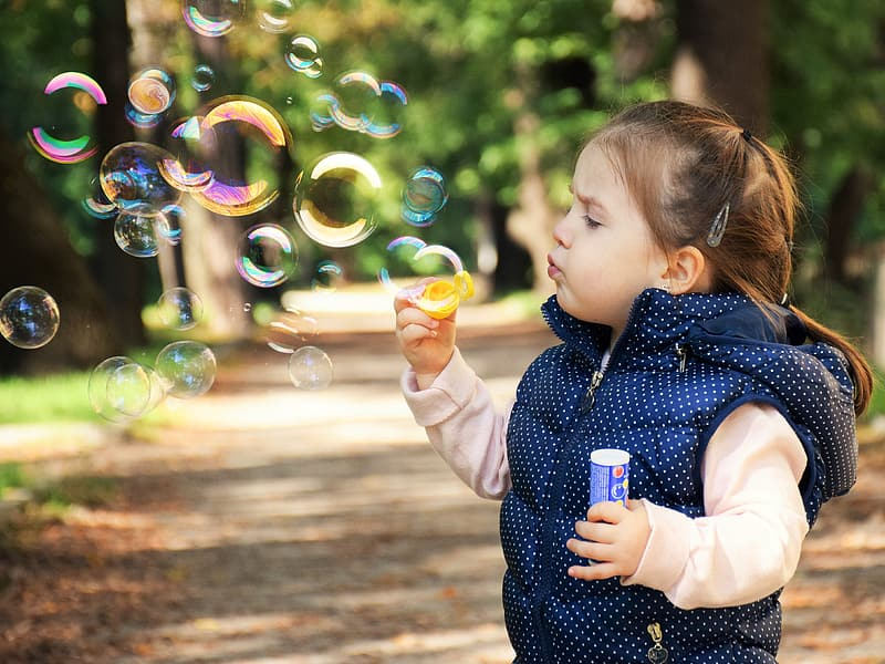 Selective focus photography of girl blowing bubbles