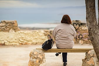 Woman in gray hoodie sitting on brown wooden bench during daytime