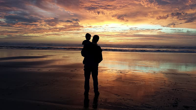 Silhouette of man carrying baby beside the seashore