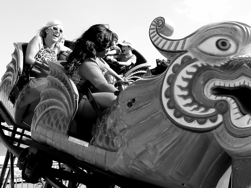Grayscale photo of people riding on a round ride