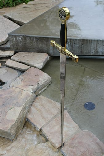 Gray stainless steel and brass-colored claymore sword in a stone