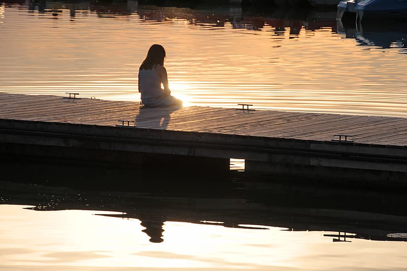 Woman in white long-sleeved shirt sits on brown wooden dock