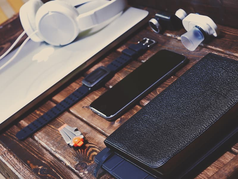 Space gray iPhone 6 beside watch on wooden surface