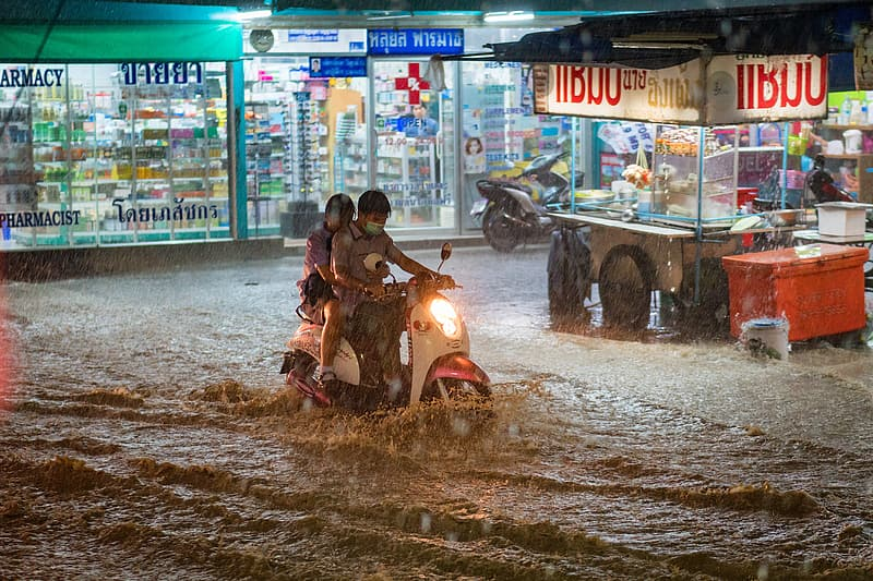 Two people on motor scooter in middle of flood