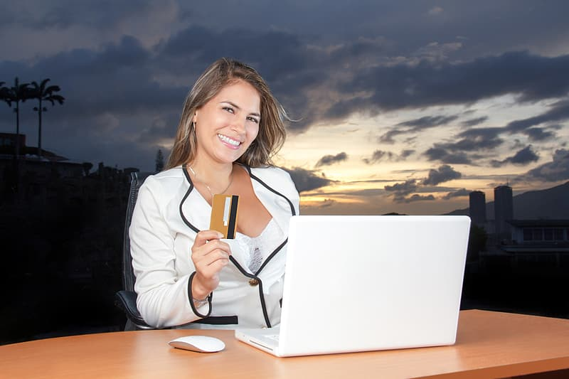 Woman wearing white blazer holding a brown and black labeled magstripe card in front of white laptop computer