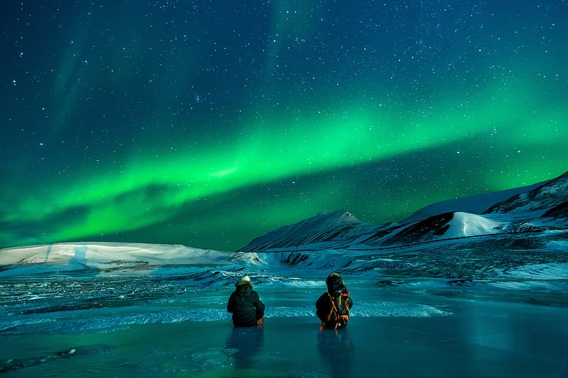 Two people partially submerged on water surrounded by snow overlooking aurora borealis