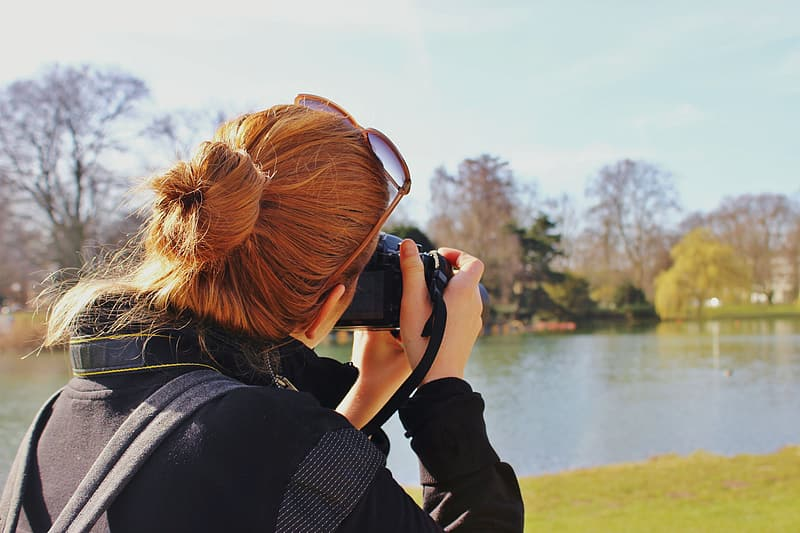 Woman in black jacket taking picture of lake