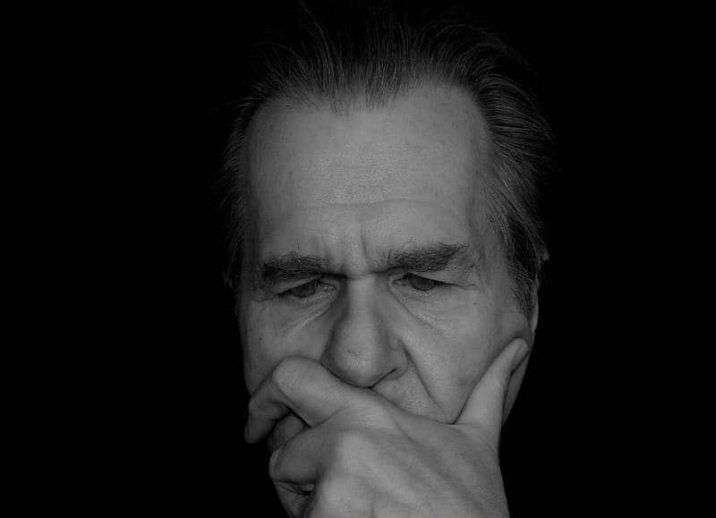 Man thinking deeply hold covering his mouth