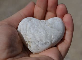 Person holding white heart stone