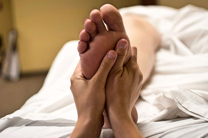 Photo of person pressing person's foot