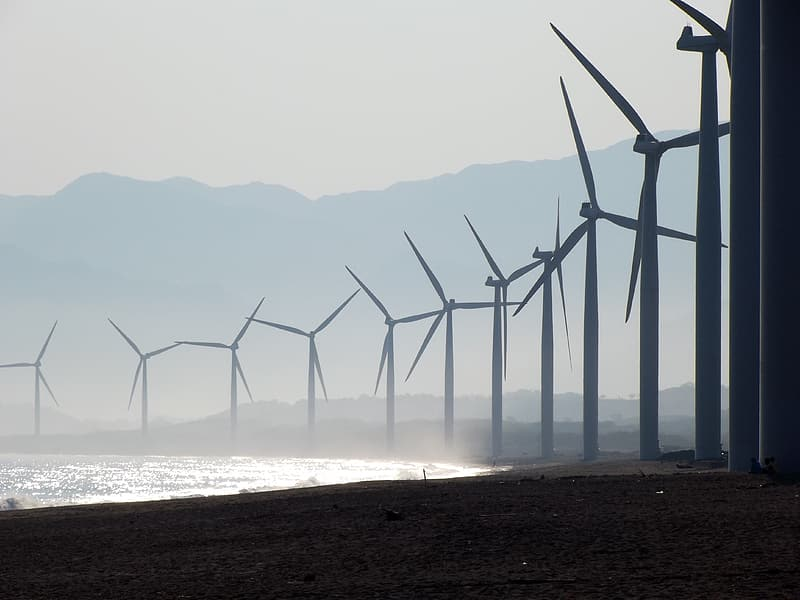 Line of windmills in front of sea at daytime