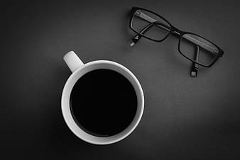 Black framed eyeglasses beside white ceramic mug