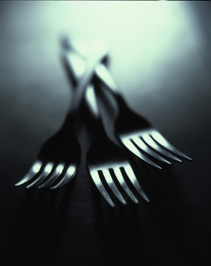 Shallow focus photography of three stainless steel forks